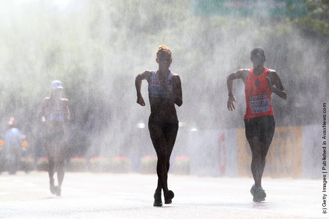 Athletes run through a mist station during the women's 20km race walk during day five of the 13th IAAF World Athletics Championships in Daegu