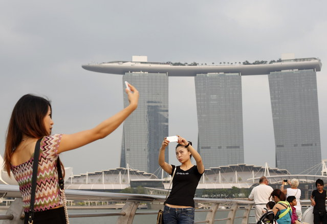 People take photos of themselves at a tourist landmark overlooking the Marina Bay Sands casino in Singapore March 4, 2014. Thick haze blanketing parts of Indonesia's Riau province continued to ground helicopters and obstruct water bombing efforts, while slight haze affected Singapore on Tuesday. (Photo by Edgar Su/Reuters)