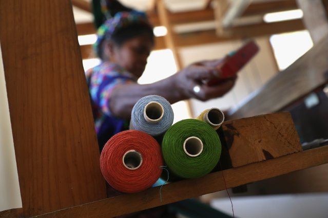 Indigenous Mayan weaver Delfina Perez, who's husband has worked in the U.S. as an immigrant for 20 years, works on a foot loom at the Grupo Cajola weaving cooperative on February 11, 2017 in Cajola, Guatemala. (Photo by John Moore/Getty Images)