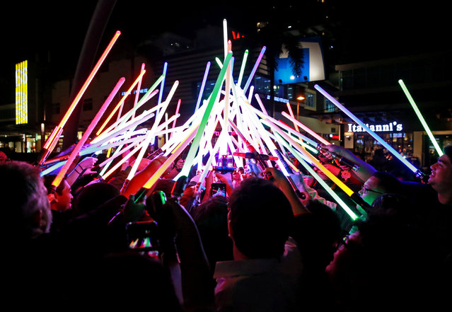 Star Wars enthusiasts huddle with their lightsabers after participating in Earth Hour at Taguig City, Philippines, March 30, 2019. (Photo by Eloisa Lopez/Reuters)