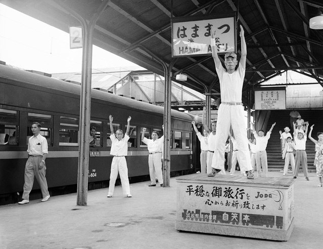Passengers on a train traveling from Tokyo to Osaka go through three minutes of calisthenics under leadership of a drill master, during a five-minute stopover at Hammamatsu on August 27, 1952. This unusual service was set up to help travelers on the long journey limber up at the station which is about half way between the two cities. There is even music for the exercises, and a platform for the drill master. (Photo by Max Desfor/AP Photo via The Atlantic)