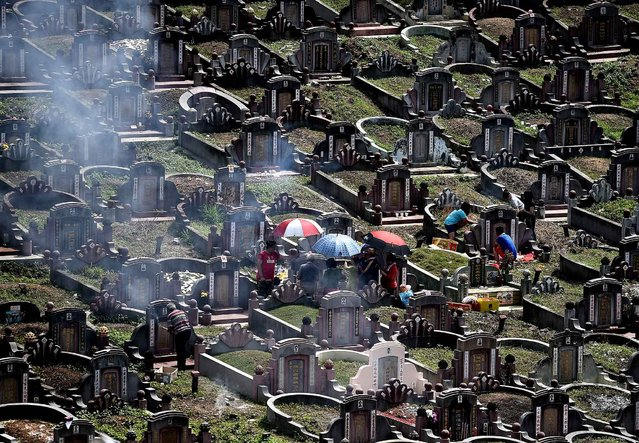 """Ethnic Chinese Malaysians visit the graves of their ancestors at a cemetery on the eve of the annual """"Qingming"""" festival in Kuala Lumpur on April 3, 2016. Qingming, also known as Tomb-Sweeping Day, is an annual Chinese festival to commemorate the dead. Families visit and clean the graves of their ancestors, burning incence, paper money and presenting offerings such as food, tea, wine and joss paper accessories. (Photo by Manan Vatsyayana/AFP Photo)"""