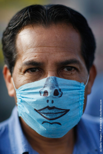 A drawing adorns the surgical mask worn by a man to help prevent being infected with the swine flu