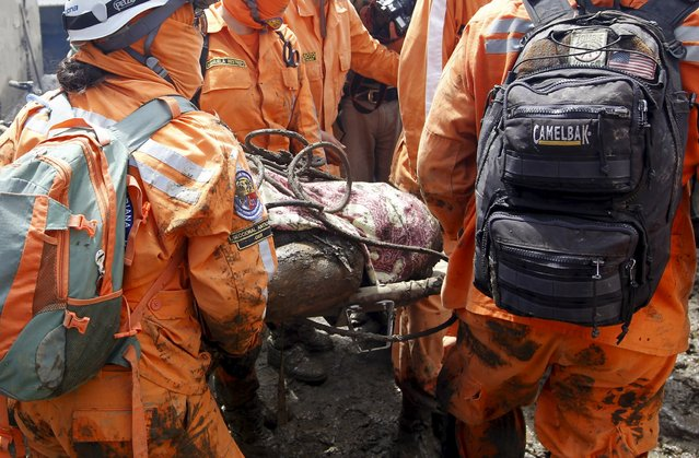 Rescue workes carry the body of a victim, after a landslide in the municipality of Salgar, in Antioquia department, May 19, 2015. (Photo by Fredy Builes/Reuters)