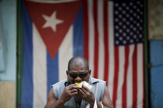 "Guillermo Manzano, 54, a welder, eats cake while posing for a photograph in front of Cuban and U.S. flags in Havana, March 23, 2016. Regarding Obama's historic visit to the island, Manzano said, ""The best, the greatest thing that has entered this country"". (Photo by Ueslei Marcelino/Reuters)"
