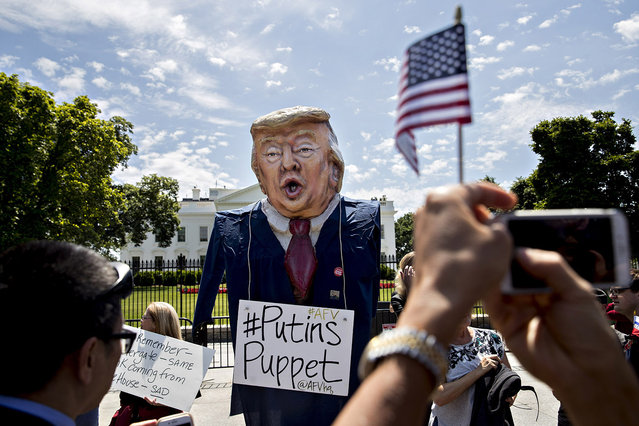 "A demonstrator wears an effigy in the likeness of U.S. President Donald Trump with a sign that reads ""Putins Puppet"" during a protest outside the White House in Washington, D.C., U.S., on Wednesday, May 10, 2017. (Photo by Andrew Harrer/Bloomberg via Getty Images)"