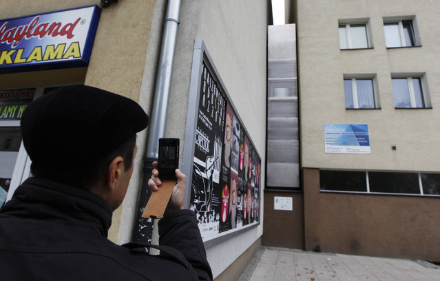 A man takes a picture of the one of the world's narrowest buildings, built as an artistic installation, wedged between two existing buildings, in Warsaw, Poland October 23, 2012. The building, just 92 cm (36 inches) wide at its narrowest point, will be a part-time home to Israeli writer Edgar Keret. (Photo by Kacper Pempel/Reuters)