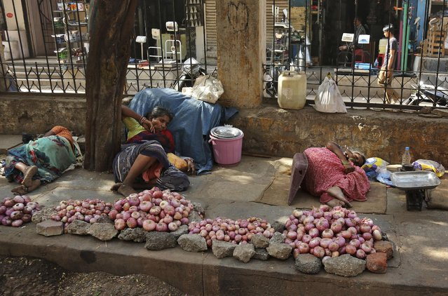 Indian vendors selling onions rest on a sidewalk under the shade of a tree on a hot summer day in Hyderabad, India, Monday, May 25, 2015. Hundreds of people have died since mid-April in a heat wave sweeping two southeast Indian states, Andhra Pradesh and Telangana, officials said Saturday. (Photo by Mahesh Kumar A./AP Photo)