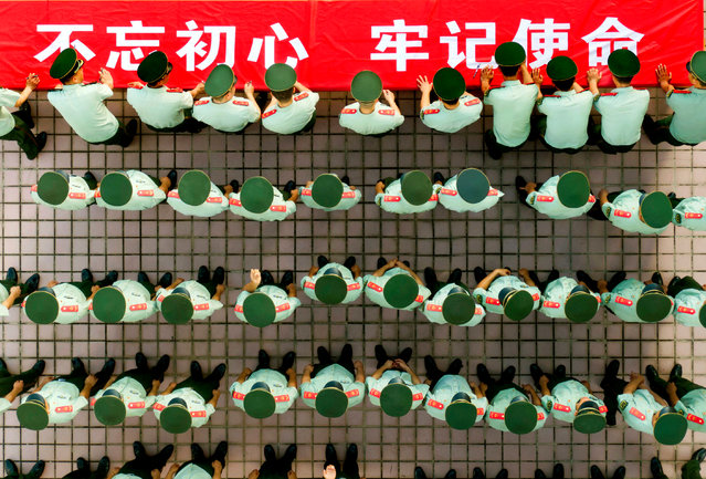 Members of the local paramilitary force sign their names on a banner marking the 98th anniversary of the Communist party in Shenzhen, China on June 30, 2019. (Photo by Feature China/Barcroft Media)