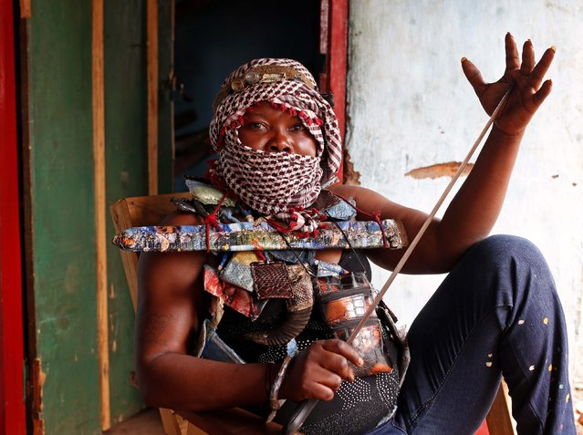 A masked female member of the anti-balaka, a Christian militia, holds a machete as she sits in a village of Zawa April 8, 2014. (Photo by Goran Tomasevic/Reuters)