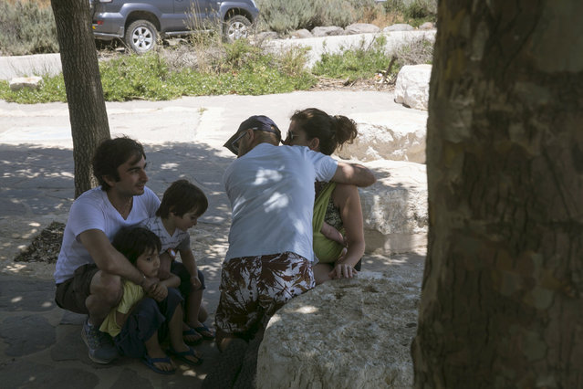 Israelis take cover as a siren warning of incoming rockets sounds in the Israeli-occupied Golan Heights, near the ceasefire line between Israel and Syria June 17, 2015.  Israel signaled readiness on Tuesday to intervene if Syrian refugees were to throng to its armistice line on the Golan Heights, after Israel's Druze Arab minority stepped up a public campaign to help brethren caught up in the civil war next door. REUTERS/Baz Ratner