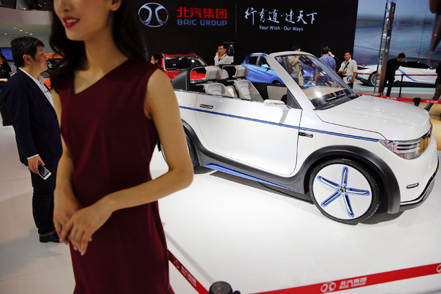 Visitors gather around vehicles presented at Beijing Automotive Group (BAIC) booth during Auto China 2016 auto show in Beijing April 25, 2016. (Photo by Damir Sagolj/Reuters)
