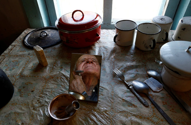 "Ivan Shamyanok, 90, shaves in his house in the village of Tulgovichi, near the exclusion zone around the Chernobyl nuclear reactor, Belarus March 15, 2016. ""My sister lived here with her husband. They decided to leave and soon enough they were in the ground ... They died from anxiety. I'm not anxious. I sing a little, take a turn in the yard, take things slowly like this and I live"", he said. (Photo by Vasily Fedosenko/Reuters)"