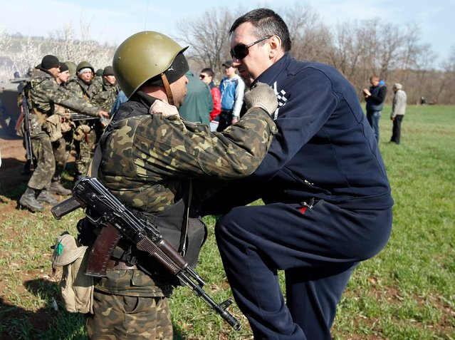 Ukrainian soldiers clash with pro-Russia protesters on the field near Kramatorsk, in eastern Ukraine April 16, 2014. Ukrainian forces tightened their grip on the eastern town of Kramatorsk on Wednesday after securing control over an airfield from pro-Russian separatist militiamen, prompting Russian President Vladimir Putin to warn of the risk of civil war. (Photo by Marko Djurica/Reuters)
