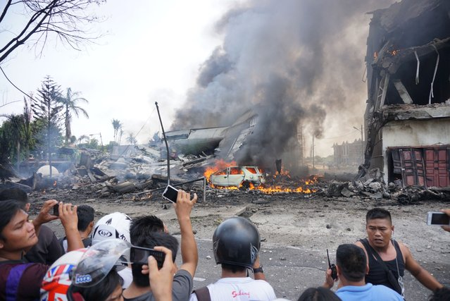 People look at a military plan crash in Medan on June 30, 2015.  An Indonesian military transport plane crashed on June 30 shortly after taking off and exploded in a ball of flames in a residential area. (Photo by Muhammad Zulfan Dalimunthe/AFP Photo)