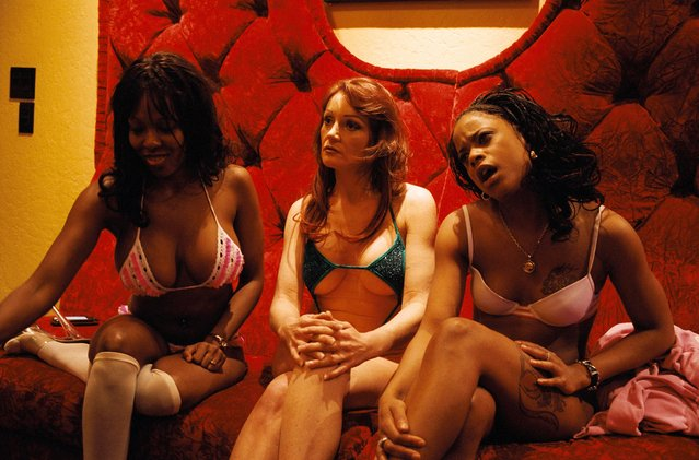 """Three working girls are having a """"girl talk"""" while waiting for customers, in the parlor at the Moonlite Bunny Ranch, a legal brothel owned by Dennis Hof, in Lyon County, one of the fews counties in the USA which permits legalized prostitution. (Photo by Stephan Gladieu/Getty Images)"""