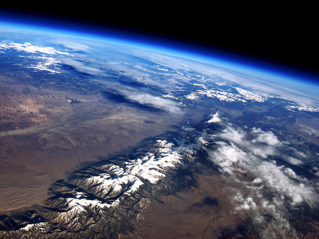 """Sangre de Cristo Range, Colorado from 98,000 feet up on a Weather Balloon"". A view east of the San Luis Valley over the Sangre de Cristo Range of south-central Colorado, USA. In the lower left-hand corner is Great Sand Dunes National Park; the highest dunes there are 750 feet tall. In the background you can make out center-pivot irrigated farm fields on the valley floor, and beyond the San Juan Range. To the north lies the Sawtooth Range. (Photo and caption by John Flaig/National Geographic Photo Contest)"