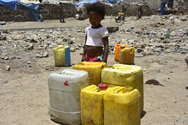A child from the Akhdam community of the large Yemeni underclass stands near jerry cans full of water outside her family's shanty in Sana'a, Yemen, 04 May 2014. Akhdam is the lowest rung in the Yemeni caste system and by far the poorest. Marginalized and shunned by mainstream society in Yemen, the servants live in small shantytowns, mostly in big cities, including Sana'a. (Photo by Yahya Arhab/EPA)