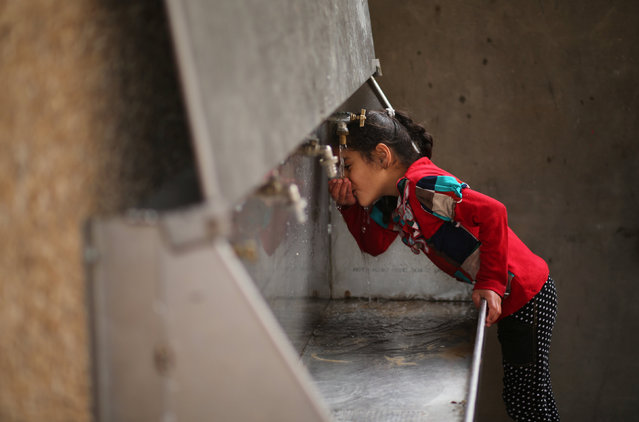 A Palestinian girl drinks water from a public tap in Jabaliya refugee camp in the northern Gaza Strip January 24, 2017. (Photo by Mohammed Salem/Reuters)