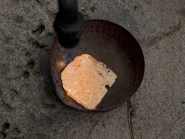 A miner melts an amalgam of gold and mercury to burn off the mercury in La Pampa in Peru's Madre de Dios region. This rudimentary process of extracting the gold from the amalgam, releases mercury vapors, adding to the contamination that is resulting in the deforestation of thousands of acres of the Amazon rainforest. (Photo by Rodrigo Abd/AP Photo)