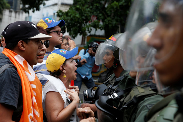 Opposition supporters shout to Venezuelan National Guards during clashes in a rally to demand a referendum to remove President Nicolas Maduro in Caracas, Venezuela, May 18, 2016. (Photo by Carlos Garcia Rawlins/Reuters)
