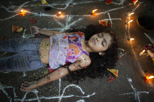 In this photo taken October 13, 2019, girl lies surrounded by candles and designs of white powder during a ceremony on Sorte Mountain where followers of indigenous goddess Maria Lionza gather annually in Venezuela's Yaracuy state. Believers congregated for rituals on the remote mountainside where adherents make an annual pilgrimage to pay homage to the goddess, seeking spiritual connection and physical healing. (Photo by Ariana Cubillos/AP Photo)