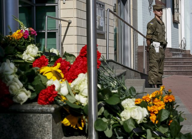 Flowers are seen outside the Dutch embassy to commemorate the victims of the downing of Malaysia Airlines MH17 in eastern Ukraine a year ago, as serviceman stands guard in Kiev, Ukraine July 17, 2015. (Photo by Gleb Garanich/Reuters)