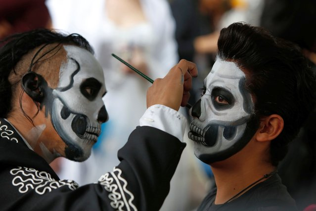 Ulises Armendariz, left, paints a customers face like a skull before the Catrinas parade down Mexico City's iconic Reforma avenue during Day of the Dead celebrations, Saturday, October 26, 2019. (Photo by Ginnette Riquelme/AP Photo)