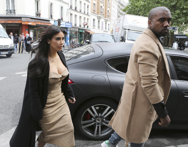 Kim Kardashian and U.S rap singer Kanye West arrive at a luxury shop in Paris, Wednesday, May 21, 2014.  The gates of the Chateau de Versailles, once the digs of Louis XIV, will be thrown open to Kim Kardashian, Kanye West and their guests for a private evening this week ahead of their marriage. (Photo by Jacques Brinon/AP Photo)