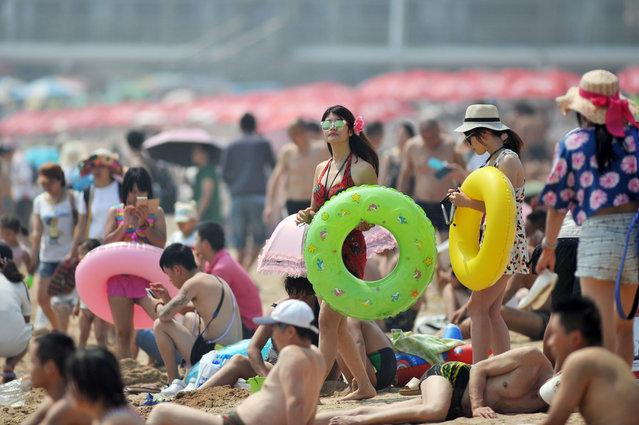 Visitors crowd a seaside beach on the first day this summer that it was open to the public in Qingdao in eastern China's Shandong province Wednesday, July 1, 2015. China's beaches are a popular destination for its citizens to escape the summer heat. (Photo by Chinatopix Via AP Photo)