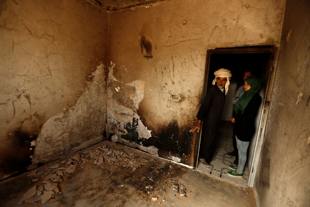 People inspect a burnt room inside their house, which was damaged by fighting between Islamic State jihadists and  government forces in Ben Guerdane, near the Libyan border, Tunisia April 12, 2016. (Photo by Zohra Bensemra/Reuters)