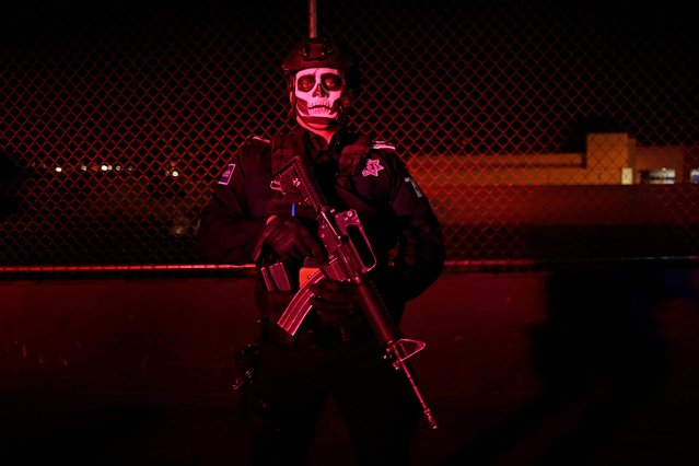 A police officer with his face painted poses for a photograph while watching the Day of the Dead parade in Ciudad Juarez, Mexico on November 2, 2019. (Photo by Jose Luis Gonzalez/Reuters)