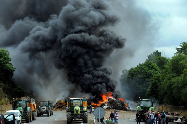 Farmers use tractors and burn tires, hay and manure as they block the highway between Morlaix and Brest during a demonstration against the market prices of their product, on July 22, 2015 in Morlaix, western of France. French farmers protesting over falling food prices threatened to step up blockades of cities, roads and tourist sites, as the government prepared to unveil emergency aid for them. (Photo by Fred Tanneau/AFP Photo)