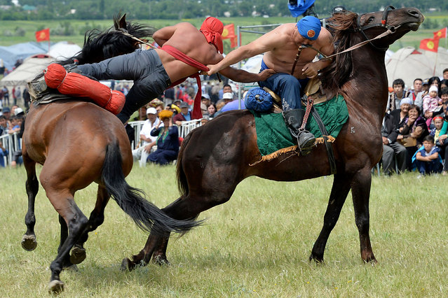 "Kyrgyz men on horseback compete during their traditional game of ""Oodarysh"" during the celebrations of the 90th anniversary formation of the Chui region in the village of Kuntu some 20 kms from Bishkek on May 27, 2016. (Photo by Vyacheslav Oseledko/AFP Photo)"