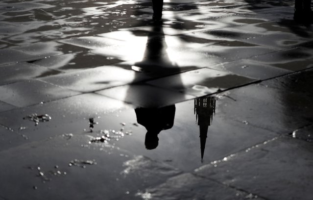 The Palace of Westminster and a man walking are reflected in a puddle in London, Britain November 4, 2019. (Photo by Yara Nardi/Reuters)