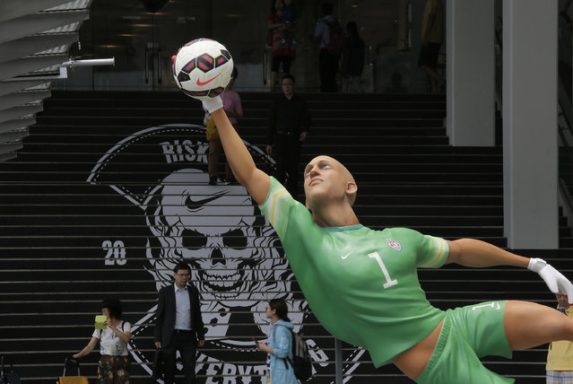A giant size figure of the United States' goalkeeper Tim Howard is displayed outside a shopping mall in Hong Kong, Thursday, June 12, 2014, to promote the upcoming 2014 World Cup in Brazil. A total of seven 3.5 meters to 4 meters (11 feet 6 inch to 13 feet one inch) tall figures of famous players attract many soccer fans. (Photo by Vincent Yu/AP Photo)