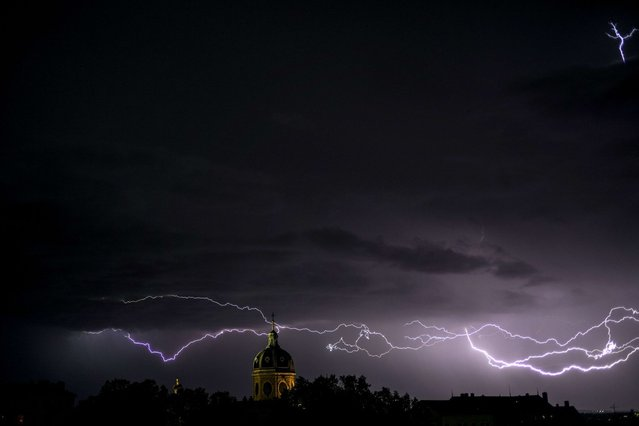 Flashes of lightning strike above the Saint-Bruno des Chartreux church in Lyon. (Photo by Jeff Pachoud/AFP Photo)