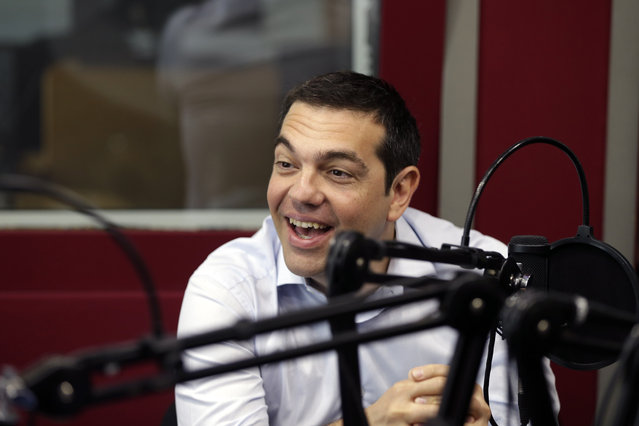 "Greece's Prime Minister Alexis Tsipras gives an interview to the radio station ""Sto Kokkino 1055"" in Athens, Wednesday, July 29, 2015. Greece's parliament has already approved two batches of reforms, drastically increasing sales tax on key consumer goods, and reforming the banking and judiciary systems. But that caused a rift within Tsipras' party, and about a quarter of his lawmakers refused to back the reforms, which were passed with the help of pro-European opposition parties. (Photo by Thanassis Stavrakis/AP Photo)"