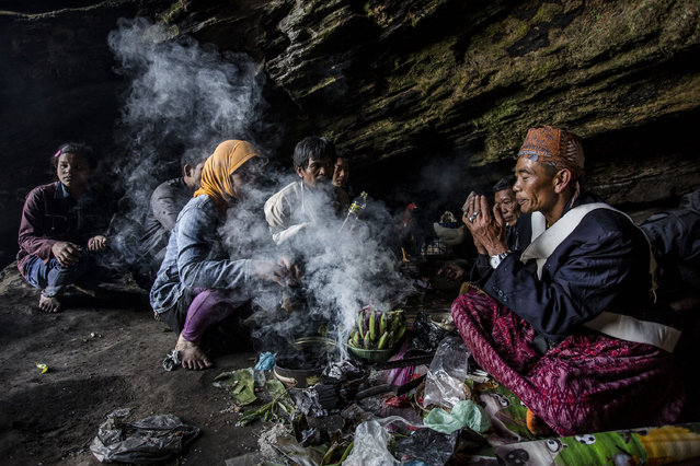 A Tenggerese shaman praying for worshippers at Widodaren cave during the Tenggerese Hindu Yadnya Kasada festival on July 31, 2015 in Probolinggo, East Java, Indonesia. The festival is the main festival of the Tenggerese people and lasts about a month. On the fourteenth day, the Tenggerese make the journey to Mount Bromo to make offerings of rice, fruits, vegetables, flowers and livestock to the mountain gods by throwing them into the volcano's caldera. (Photo by Ulet Ifansasti/Getty Images)