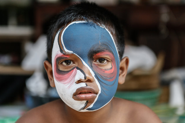 A boy with a painted face poses before the Grebeg Ritual on June 25, 2014 in Tegallalang Village, Gianyar, Bali, Indonesia. During the biannual ritual, young members of the community parade through the village with painted faces and bodies to ward off evil spirits. (Photo by Putu Sayoga/Getty Images)