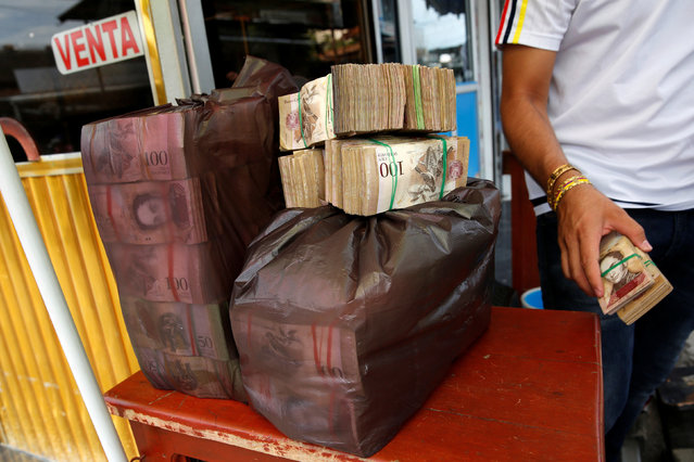 Plastic bags filled with Venezuelan bolivar notes are seen on a currency trader's table on a street in Puerto Santander, Colombia, June 3, 2016. (Photo by Carlos Garcia Rawlins/Reuters)