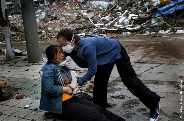 A Chinese woman is helped by a stranger as she collapses after viewing the site of her familys home for the first time since the earthquake on May 12 in the town of Hanwang May 25, 2008