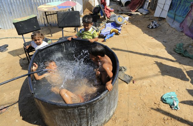 Palestinian children cool off in a makeshift plastic pool in the yard of the ruins of their family house which was destroyed in the last summer's Israel-Hamas war, in Beit Hanoun, in the northern Gaza Strip, Thursday, July 30, 2015 where the temperature reached 36 degrees Celsius (97F). (Photo by Adel Hana/AP Photo)