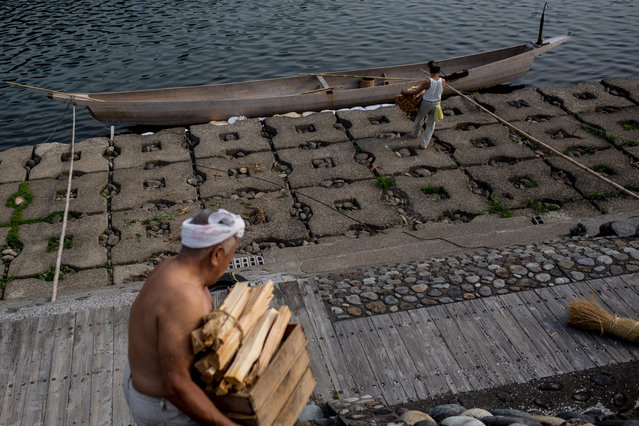 """Boatmen prepare wood to burn in the fishing boat torches ahead of the nights """"Ukai"""" Cormorant master, Mr. Masahiko Sugiyama uses sea cormorants to catch sweetfish on July 2, 2014 in Gifu, Japan. In this traditional fishing art """"ukai"""", a cormorant master called """"usho"""" manages cormorants to capture ayu or sweetfish. The ushos of River Nagara have been the official staff of the Imperial Household Agency of Japan since 1890. Currently six imperial fishermen of Nagara River conduct special fishing to contribute to the Imperial family eight times a year, on top of daily fishing from mid-May to mid-October. (Photo by Chris McGrath/Getty Images)"""