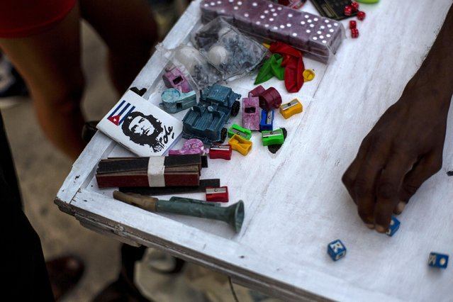 In this March 20, 2015 photo, children play dice on a table with the winners' prizes sitting on the side, at a youth fair in the Chicharron neighborhood of Santiago, Cuba. In Santiago, cell phones remain a rare luxury and public Internet is available in one state center and one hotel. (Photo by Ramon Espinosa/AP Photo)