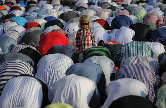 A child stands among Muslims taking part in Eid al-Fitr prayers in Bucharest, Romania,, Sunday, June 25, 2017. Members of the Romania Muslim community joined prayers at the Dinamo stadium in the Romanian capital, in the largest Muslim public gathering of the year which marks the end of the holy fasting month of Ramadan. (Photo by Vadim Ghirda/AP Photo)