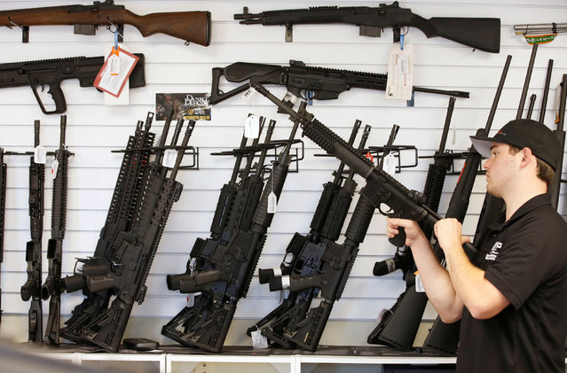 """Salesman Ryan Martinez clears the chamber of an AR-15 at the """"Ready Gunner"""" gun store in Provo, Utah, U.S., June 21, 2016. (Photo by George Frey/Reuters)"""
