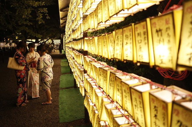 Women in kimonos look at pictures they took in front of paper lanterns during the annual Mitama Festival at the Yasukuni Shrine in Tokyo July 13, 2014. Over 30,000 lanterns light up the precincts of the shrine, where more than 2.4 million war dead are enshrined, during the four-day festival. The festival goes on till July 16. (Photo by Yuya Shino/Reuters)