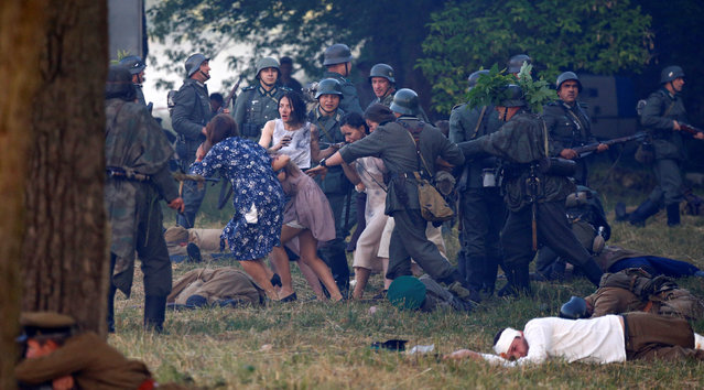 Military enthusiasts dressed as Nazi troops and Soviet Red Army and civilians take part in a re-enactment of a World War II battle at the Hero fortress as they mark the 75th anniversary of the Nazi Germany invasion, in Brest, Belarus June 22, 2016. (Photo by Vasily Fedosenko/Reuters)