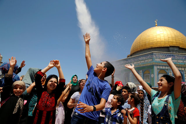 Palestinian men spray water on children to cool them down before prayers on the third Friday of the holy month of Ramadan near the Dome of the Rock, on the compound known to Muslims as Noble Sanctuary and to Jews as Temple Mount, in Jerusalem's Old City, June 24, 2016. (Photo by Ammar Awad/Reuters)